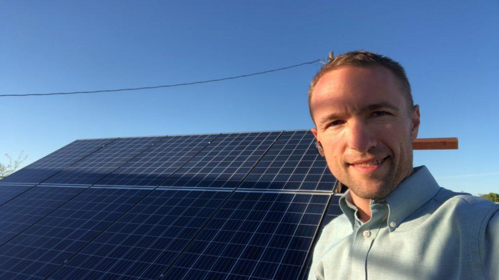 man standing alongside solar pane.s